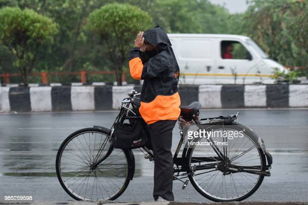 A man covers himself with a rain jacket during the premonsoon showers near Sheikh Sarai on June 27 2018 in New Delhi India The monsoon rains are...