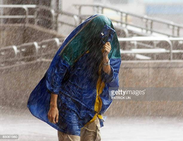 A man covers himself with a raincoat while struggling against strong winds and heavy rains brought by powerful Typhoon Jangmi in Taipei on September...