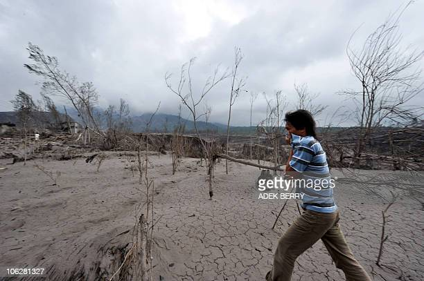 A man covers his face as he examines the scene after the eruption on October 26 of Mount Merapi volcano in Kali Adem village in Sleman on October 28...