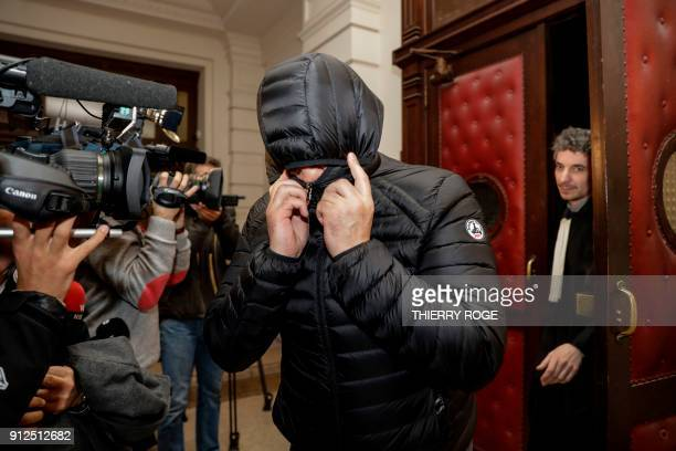 A man covers his face as he leaves the court during the first session of the 2013 Brussels Airport diamond heist case at the Brussels criminal court...