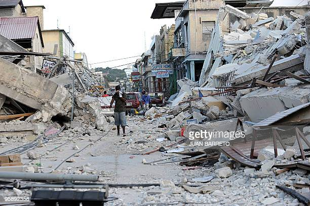 A man covers his face as he walks amid the rubble of a destroyed building in PortauPrince on January 14 following the devastating earthquake that...