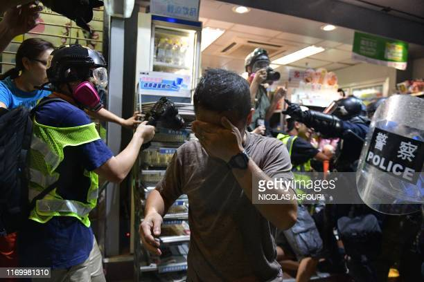 A man covers his face as riot police use pepper spray during clashes with prodemocracy protesters in Yeun Long district in Hong Kong on September 21...