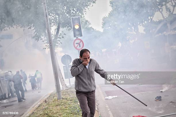 Man covers his face as Turkish anti-riot police fire tear gas during a May Day rally in Istanbul's Bakirkoy district on May 1, 2016 in Istanbul,...