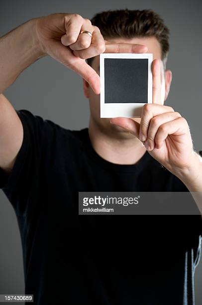 Man covers his face by holding up an instant picture