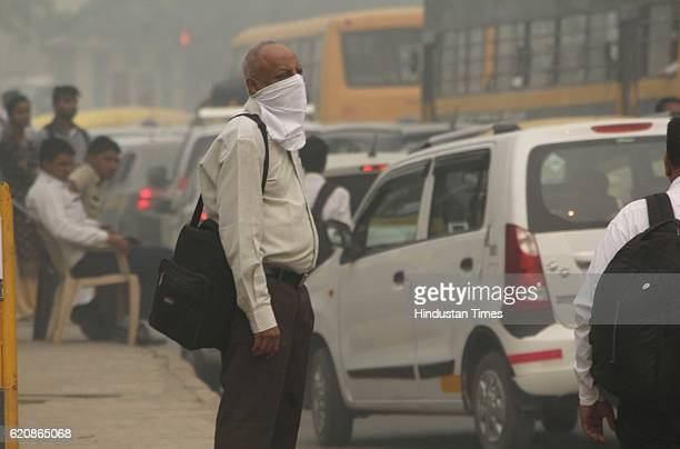 A man covers his face on smoggy morning as city covered under a blanket of heavy smog air quality deteriorated sharply overnight leading to poor...