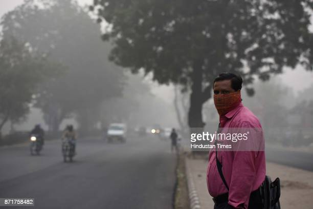 A man covers his face to avoid pollution amid heavy smog on November 8 2017 in New Delhi India Delhi was enveloped in a thick blanket of haze for the...