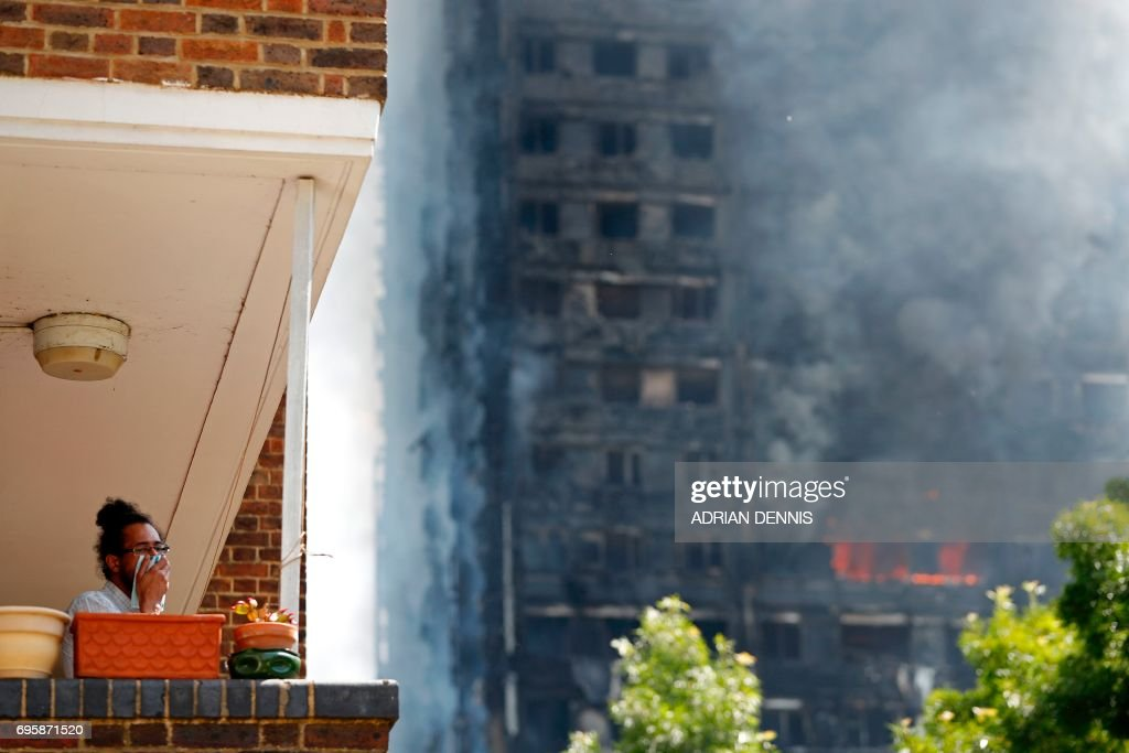 A man covers his face with a cloth as smoke billows from Grenfell Tower, a residential block of flats on June 14, 2017 in west London, as firefighters continue to control a fire. Shaken survivors of a blaze that ravaged a west London tower block told Wednesday of seeing people trapped or jump to their doom as flames raced towards the building's upper floors and smoke filled the corridors. / AFP PHOTO / Adrian DENNIS