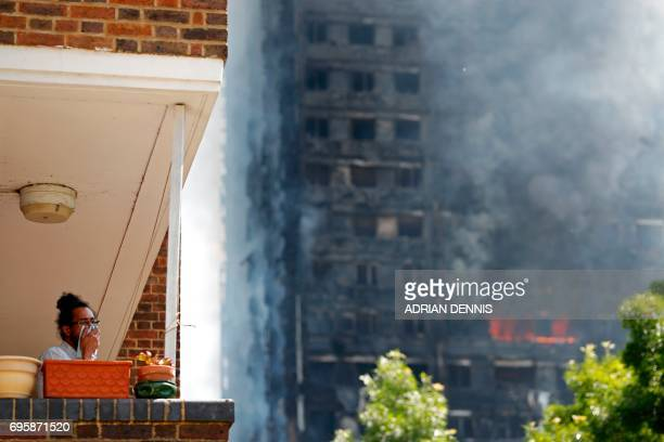 A man covers his face with a cloth as smoke billows from Grenfell Tower a residential block of flats on June 14 2017 in west London as firefighters...