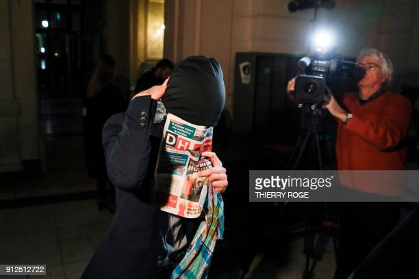 A man covers his face with a newspaper as he arrives at the court during the first session of the 2013 Brussels Airport diamond heist case at the...