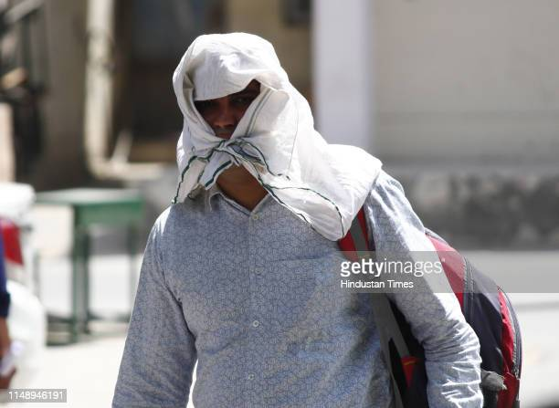 Man covers his face with a piece of cloth to beat the heat on a summer day on June 10, 2019 in Gurugram, India.