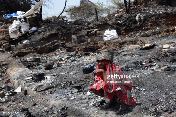 A man covers his head to avoid scorching sun at fire site in which around 1000 shanties burnt down and turned into ashes on Monday night at...