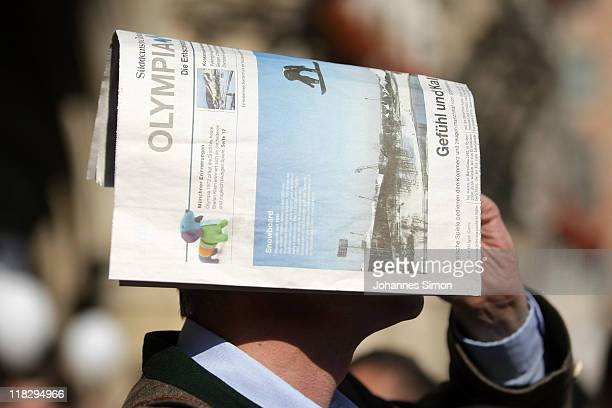 A man covers his head with a newspaper after the final decision during the public viewing for the IOC decision on 2018 olympic winter games on July 6...