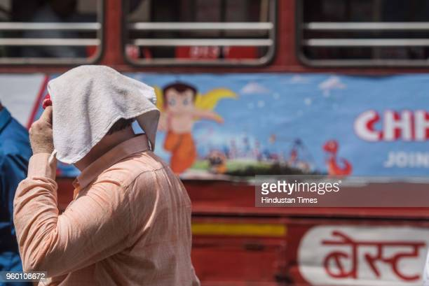 A man covers his head with handkerchief due to heat at Dadar on May 17 2018 in Mumbai India With heat wave conditions prevailing in many parts of...