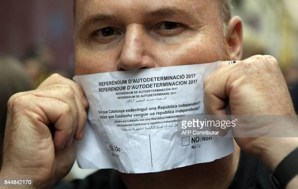 A man covers his mouth with a ballot for the Catalan referendum on independence during a protest against a police search in the headquarters of the...