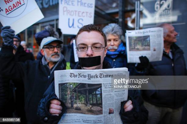 A man covers his mouth with tape as he takes part in a protest outside the New York Times on February 26 2017 in New York The White House denied...