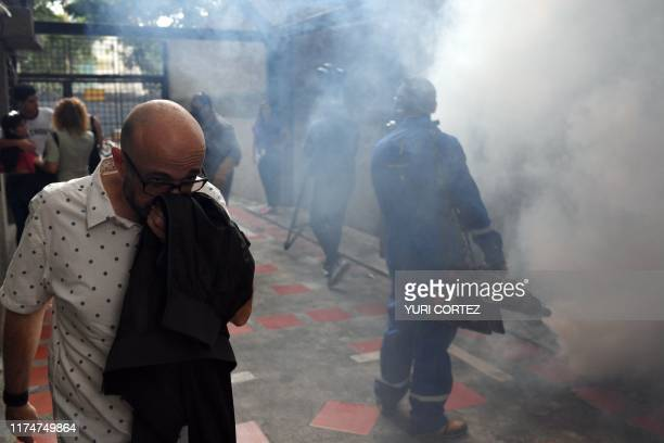 A man covers his nose as he walks past municipal workers fumigating against the aedes aegypti mosquito vector of dengue fever Zika fever and...