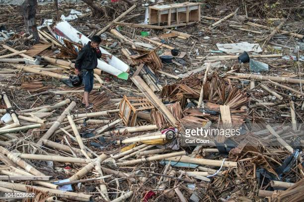 A man covers his nose as he walks through the rubble and debris of a building that was destroyed by a tsunami on October 01 2018 in Palu Indonesia...