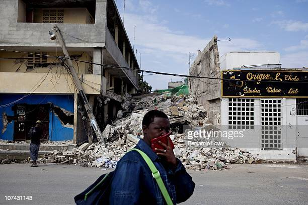 Man covers his nose to protect from the smell of decay as he walks through the remains of earthquake ravaged downtown Port au Prince, Haiti on...