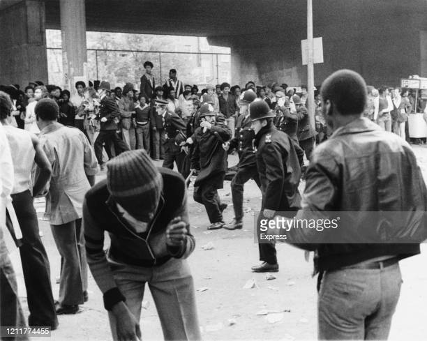 A man cowers as a line of police moves in to tackle rioters during the riots at the Notting Hill Carnival London UK 31st August 1976
