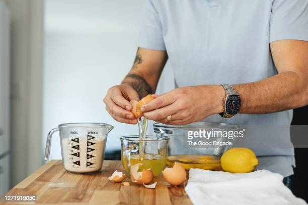 man cracking an egg into a bowl - measuring cup stock pictures, royalty-free photos & images