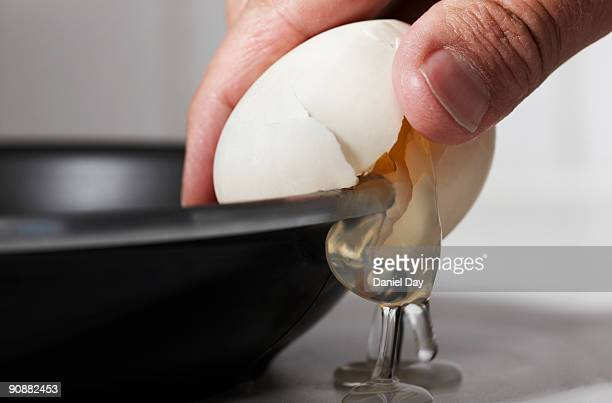 Man cracking egg on side of bowl