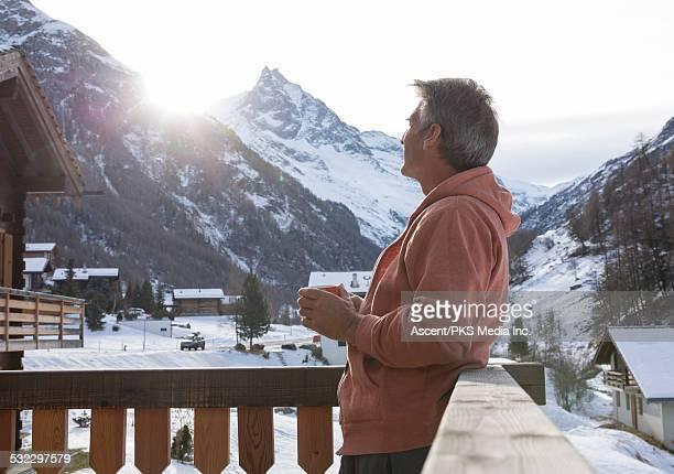 Man cradles hot drink on chalet veranda, sunrise