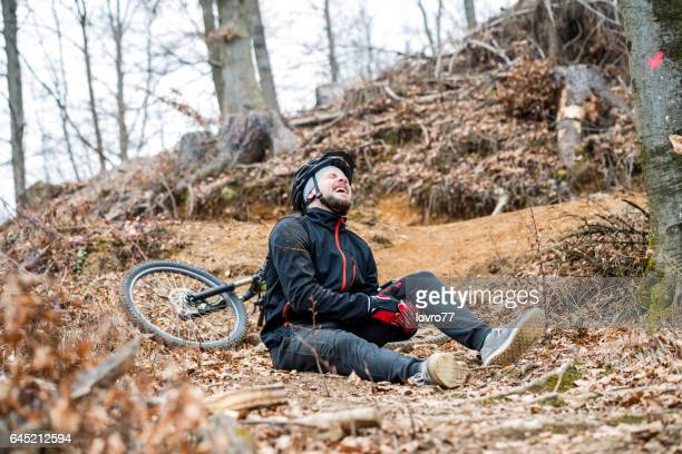 Man crashing with mountain bike in the forest