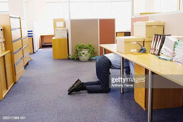 man crawling under table in office - unterhalb stock-fotos und bilder