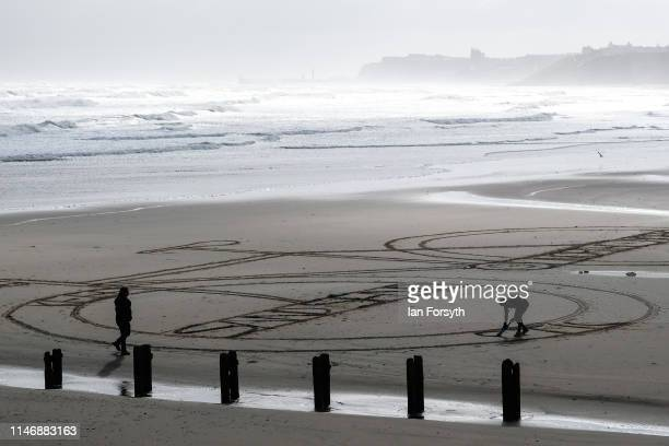A man creates a sand drawing of a bike on the beach at Sandsend ahead of the start of day 2 of the Tour de Yorkshire cycling race on May 04 2019 in...