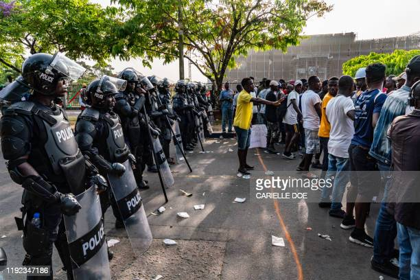 Man creates space between protesters and the police while Members of the Council of Patriots protest against the deepening economic crisis under...