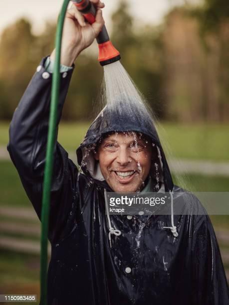 homme créant la pluie avec le tuyau de jardin dans le imperméable - pluie humour photos et images de collection