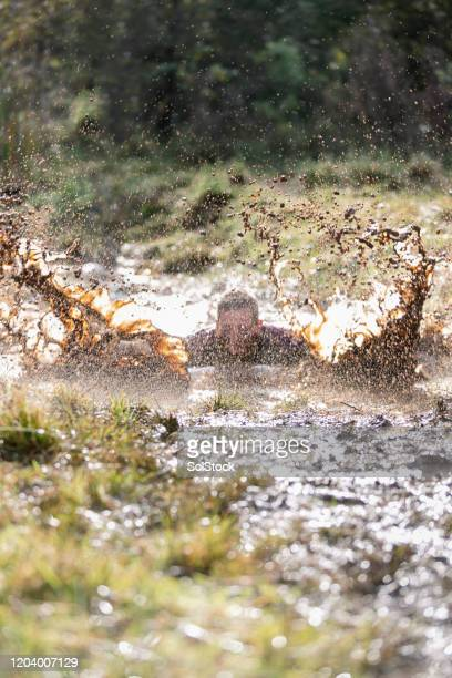 man creating splash in muddy water - one mid adult man only stock pictures, royalty-free photos & images