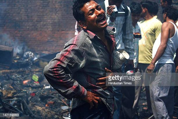 Man cries after identifying the body of his child after a fire incident at Navada village, Sector-62 on March 31, 2012 in Noida, India. Reportedly,...