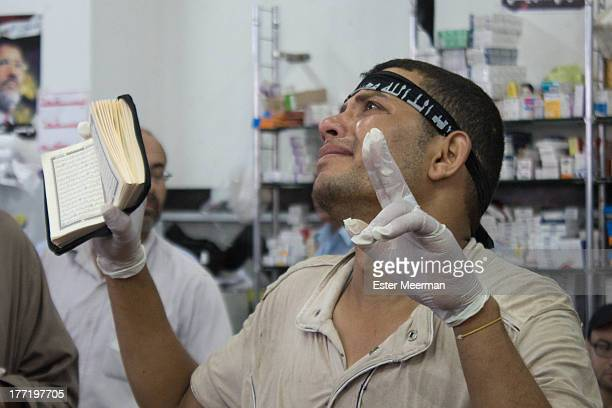 CONTENT] A man cries as he holds up a Quran and makes a peace sign in the field hospital at the Rabaa Al Adaweyya mosque in the district of Nasr on...