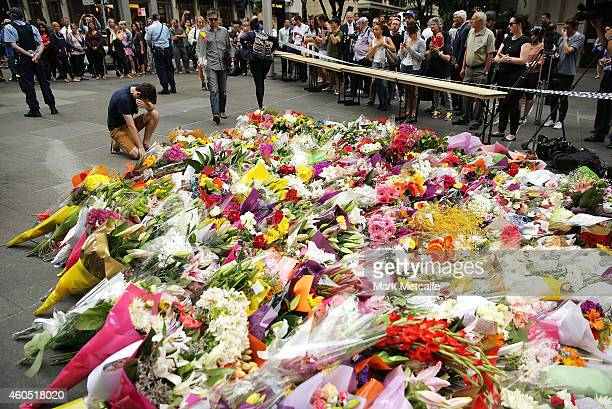 A man cries as he pays his respect at Martin Place on December 16 2014 in Sydney Australia The siege in Sydney's Lindt Cafe in Martin Place is over...