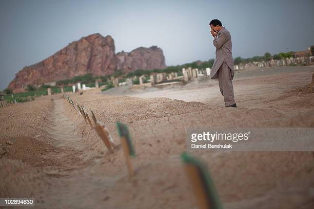 A man cries as he prays at the graves of the victims from the May Lahore attacks against Ahmadiyya community mosques July 14 2010 in Chenab Nagar...