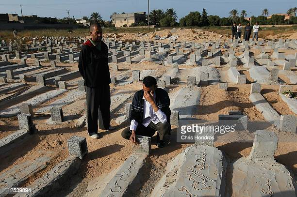 A man cries in a graveyard during the funeral of Nasser Ali Afglio a young Libyan rebel killed during battle with government troops loyal to Libyan...