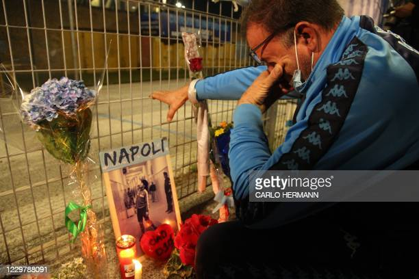 Man cries in front of a makeshift shrine set up at the main entrance of the San Paolo stadium in Naples on November 25 with an image of Argentinian...