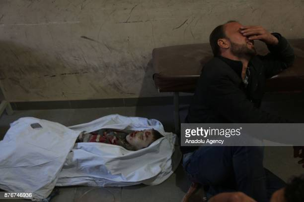 A man cries near a dead body of a child at a sahra hospital after Assad regime's warcrafts carried out airstrikes over residential areas of Kafr...