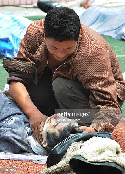 A man cries over the body of his teenage son at a makeshift morgue after a high school building collapsed after a 78 magnitude earthquake hit the...