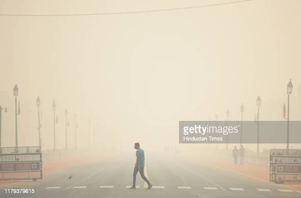 A man cross a road engulfed with smog at Rajpath on November 1 2019 in New Delhi India While Delhi's air quality plummetted on Friday its...