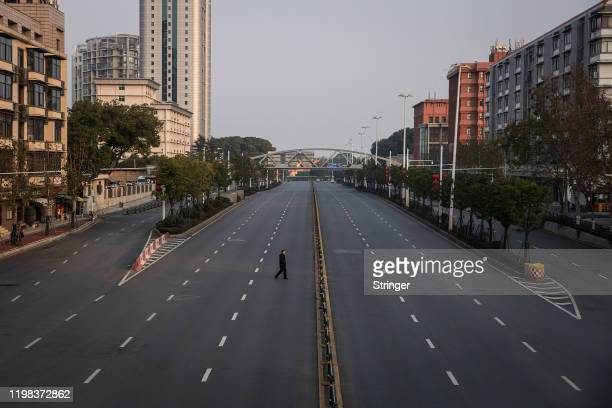 A man cross an empty highway road on February 3 2020 in Wuhan Hubei province China The number of those who have died from the Wuhan coronavirus known...