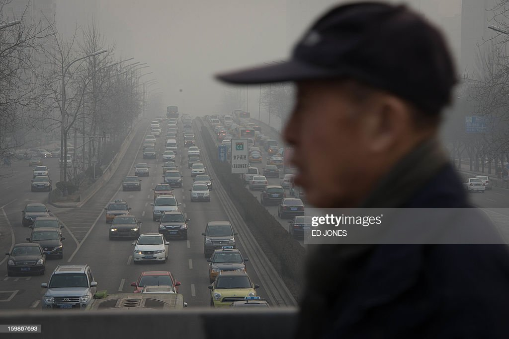 A man crosses a bridge before heavy traffic and pollution, in Beijing on January 22, 2013. Beijing has the worst traffic jams in the world, as record traffic levels take their toll on people's health, productivity and social lives, a study by IBM reported early January. Beijing and Mexico City scored 99 out of 100 in IBM's commuter pain index, followed by Johannesburg, Moscow and New Delhi. AFP PHOTO / Ed Jones