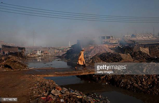 A man crosses a bridge over a polluted canal which empties out into the Buriganga river November 10 2013 in the Hazaribagh neighborhood of Dhaka...