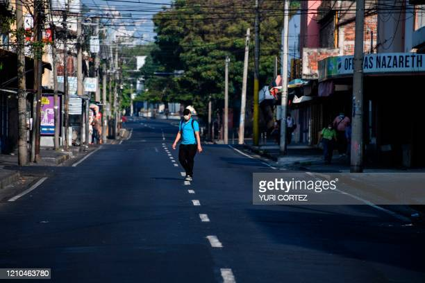 Man crosses a desolate street in the historic centre of San Salvador, inside a sanitary perimeter imposed by the capital's municipality to prevent...