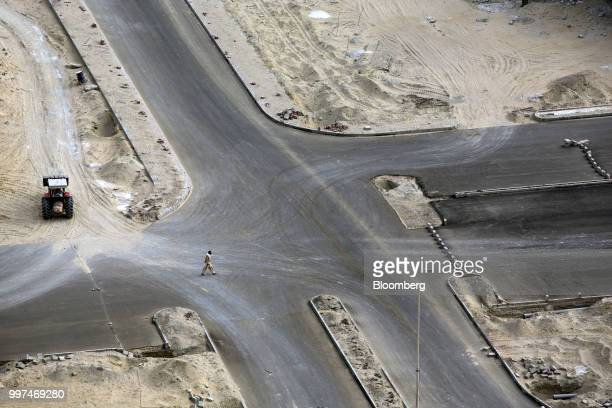 A man crosses a road next to a development site operated by China Overseas Ports Holding Co near Gwadar Port in Gwadar Balochistan Pakistan on...