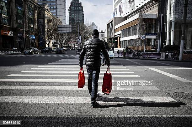 A man crosses a street carrying shopping bags in Shanghai China on Sunday Jan 24 2016 For all the hand wringing over China's economic slowdown the...