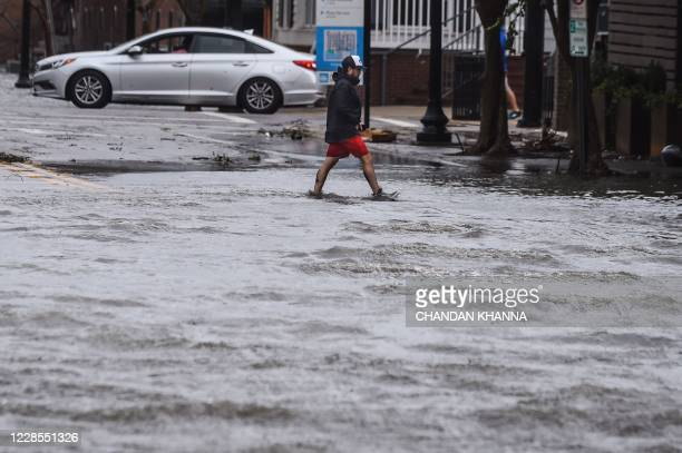A man crosses a street flooded by Hurricane Sally in Pensacola Florida on September 16 2020 Hurricane Sally barrelled into the US Gulf Coast early...
