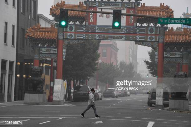 Man crosses a street in downtown Portland, Oregon where air quality due to smoke from wildfires was measured to be amongst the worst in the world,...