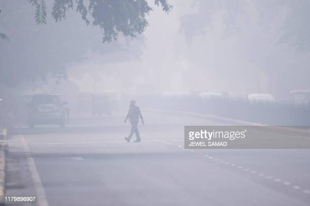 Man crosses a street in smoggy conditions in New Delhi on November 4, 2019. - Millions of people in India's capital started the week on November 4...